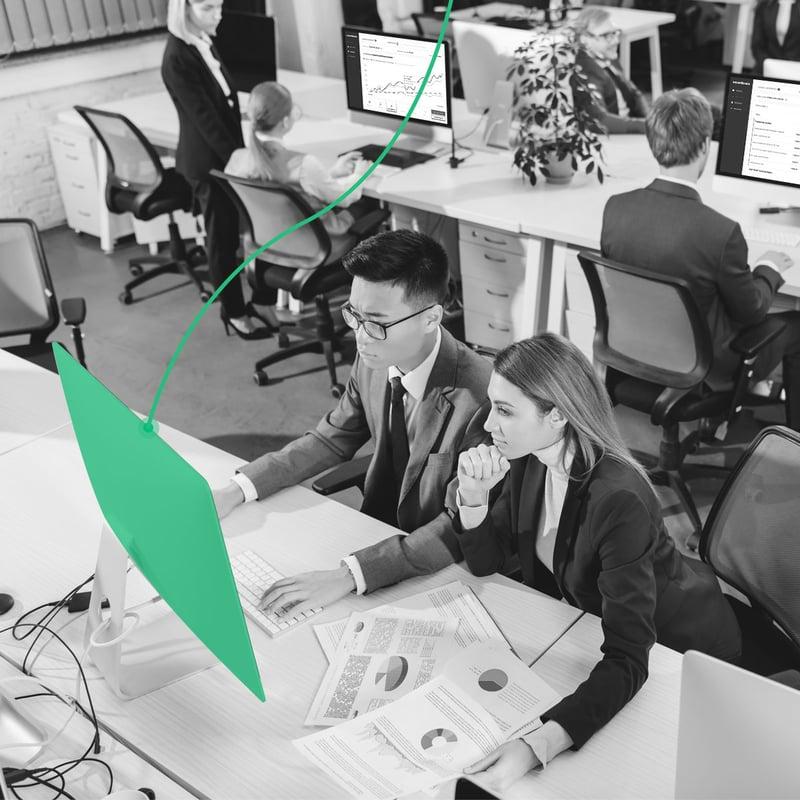 Assessores de investimentos em um escritório acompanhando o portfólio de seus clientes